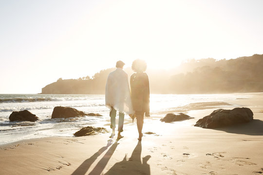 Mixed race couple walking in the sand at the beach