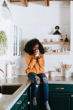 Happy Woman Holding Coffee Mug in Kitchen