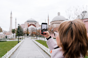Anonymous female taking picture of beautiful mosque