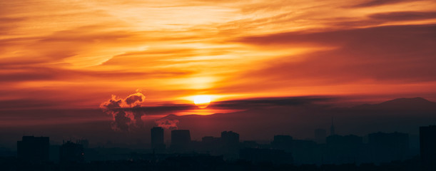 Panoramic city sunrise with polluting chimneys