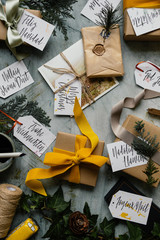 Overhead shot of christmas gifts and tags with message in many different languages
