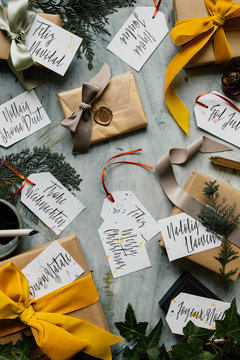 """Gifts from Christmas decorated with mustar, sage and taupe velevt and silk ribbons and hand written tags with """"Merry Christmas"""" spelt in multiple languages"""