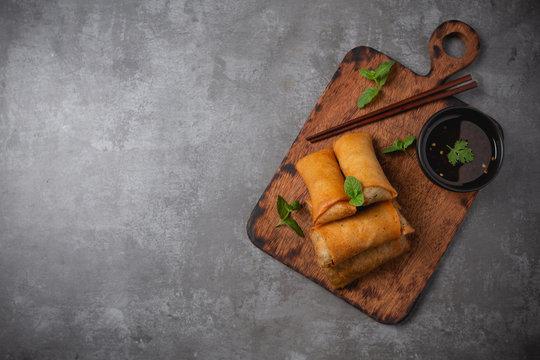 Fried spring rolls on cutting board.