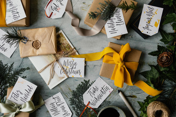 Handwritten tags with Merry Christmas written in several different languages and presents