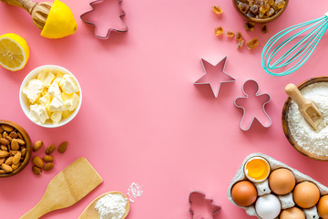 Cooking for Christmas or New Year dinner. Ingredients and utensil on pink background top view space for text