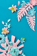 Handcraft creative decorative floral corner frame made of paper flowers and leaves, card for invitation with various leaves on a blue. Flat lay