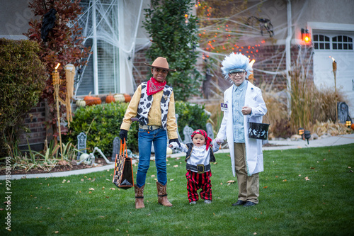Group of kids dressed in Halloween costumes going trick or treating outdoors in October in a decorated neighborhood