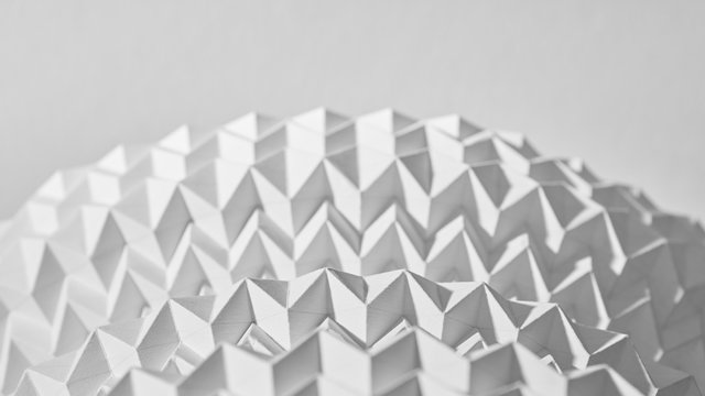 A pattern of embossed white semi-circle paper presented on a gray background with copy space. Macro photo