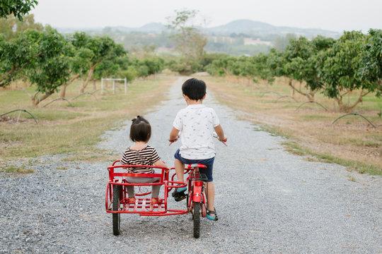 Siblings riding tandem bicycle