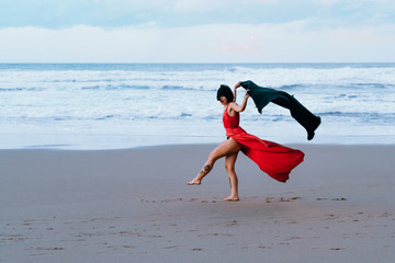 woman in red dress plays with a black blanket on the seashore