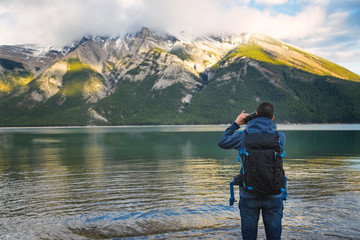 Man Taking picture with reflex camera in Minnewanka lake , Canadian Rockies, Banff Alberta Canada