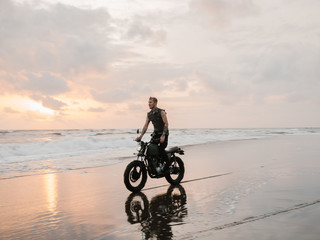 Motorcycle driving on the beach Young man on motorbike looking away