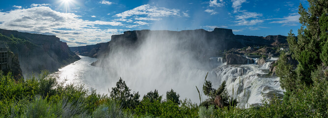 Shoshone Falls Park on bright, sunny summer day with mist and rainbow over waterfall, Twin Falls, Idaho, USA