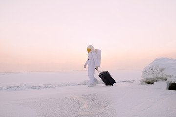 Astronaut walking with suitcase on winter planet
