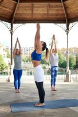 Women training yoga on terrace