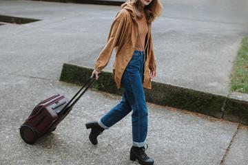 Woman Pulling Luggage on Pavement