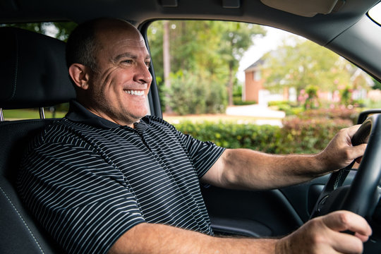 Man smiling inside truck looking out windshield