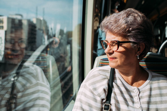Woman looking out of the subway window, sun flare