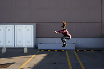Jumping squat in parking lot.