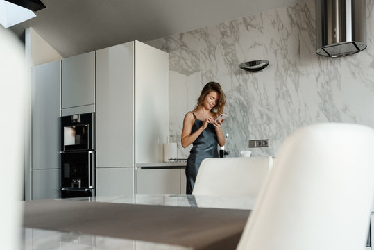 Woman with phone in modern kitchen