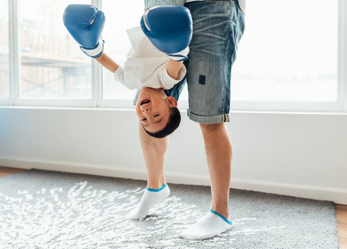 Father and son playing boxing at home