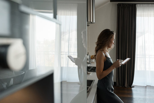Woman with coffee and phone in kitchen