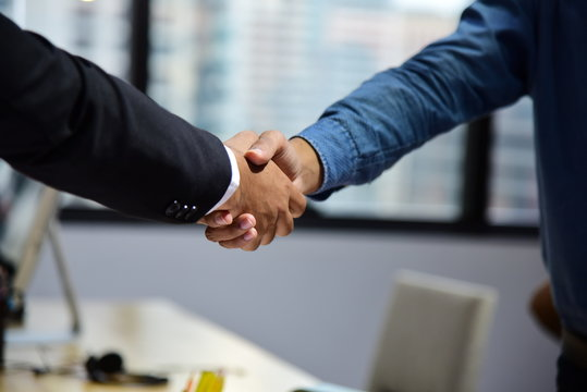 Business people making agreement and shaking hands during meeting in the office for successful dealing