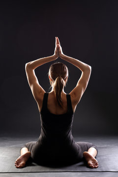 Young woman wearing black sportswear practicing yoga, doing asana Hero Pose. sitting between the knees, hands up. Virasana, Vajrasana. sporty girl working out at home or in yoga studio. view from back