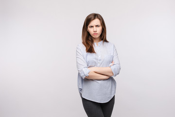 Studio portrait of disappointed young girl in striped casual shirt and black trousers looking at camera and frowning her eyebrows with folded arms on chest.