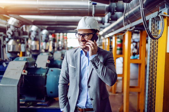 Attractive smiling caucasian businessman in suit and with helmet on head talking on the phone while standing in power plant.
