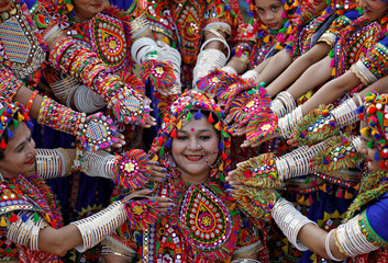 Participants dressed in traditional attire pose for pictures during rehearsals for Garba in preparations for upcoming Navratri festival in Ahmedabad