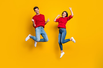 Full length photo of cheerful woman and man jump raise fists scream yes celebrate victory wear red sweater denim jeans isolated over yellow background Wall mural