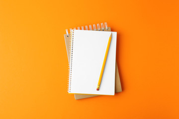Notebooks with pencil on orange background, top view