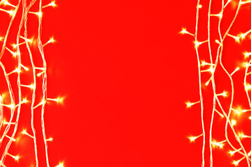 Christmas lights on red background, top view. Space for text