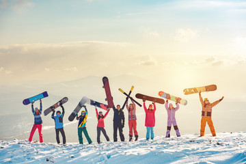 Happy friends skiers and snowboarders at ski resort Wall mural