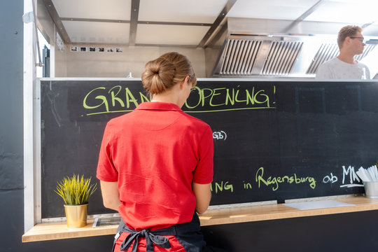 Woman writing dishes of the day on blackboard in front of food truck