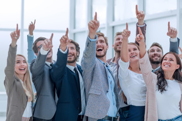 group of happy young business people pointing upwards