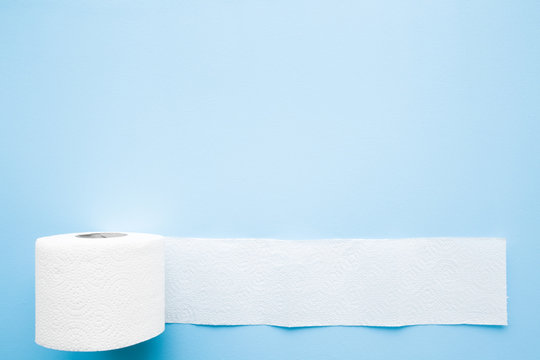 Soft, white toilet paper roll on light pastel blue background. Hygiene concept. Empty place for text, object or logo.