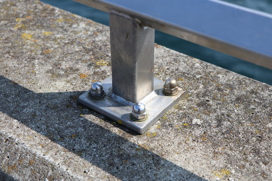 Closeup of a metal railing screwed tightly on concrete at a harbour pier