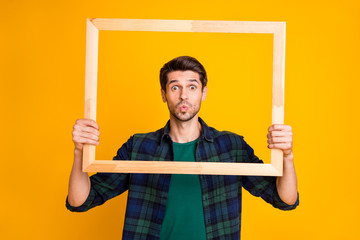 Photo of funny guy holding wooden picture frame looking through it sending air kiss wear casual plaid shirt isolated yellow color background