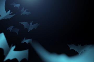 Halloween image of blue paper bats on blank dark blue background.