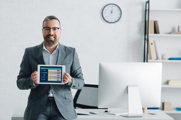 handsome businessman in formal wear holding digital tablet with sports bet website