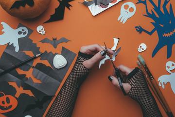 Photo of halloween backgrounds with paper ghosts, pumpkin, skulls, human hands