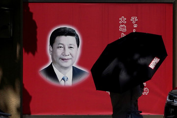 A woman walks with an umbrella past a picture of Chinese President Xi Jinping on a street in Shanghai
