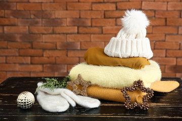 Winter clothes with Christmas decor on wooden table