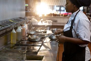 Woman frying in restaurant kitchen