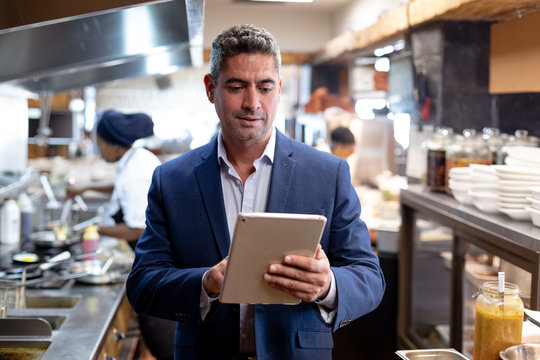 Restaurant manager using a tablet in a kitchen