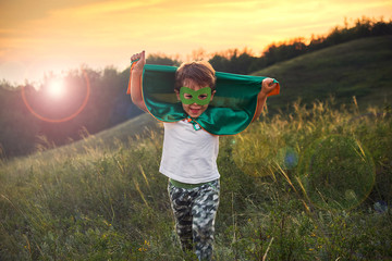 little boy playing a superhero. Kid in an Superhero's costume. happy child runs to meet the photographer.