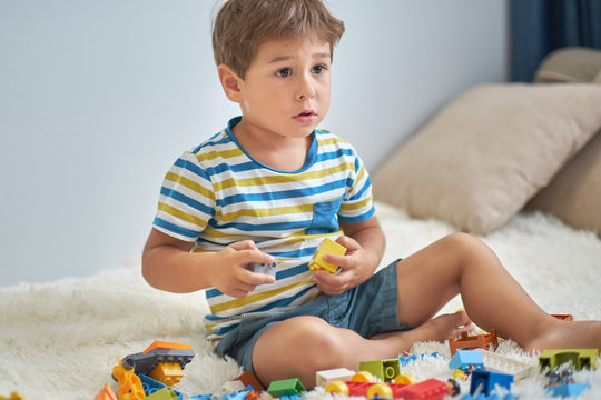 happy asian boy playing with colorful construction plastic blocks on white Bed at home.