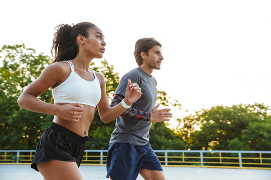 Photo of concentrated beautiful couple running together